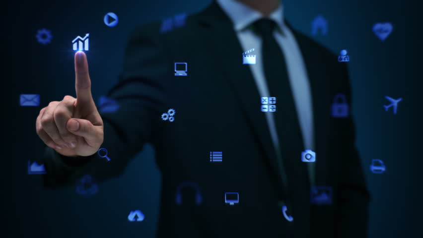 Businessman working on holographic interface. Financial. Blue. Man touching a visual screen with holographic computer icons. Financial diagrams appearing. More color options in my portfolio.