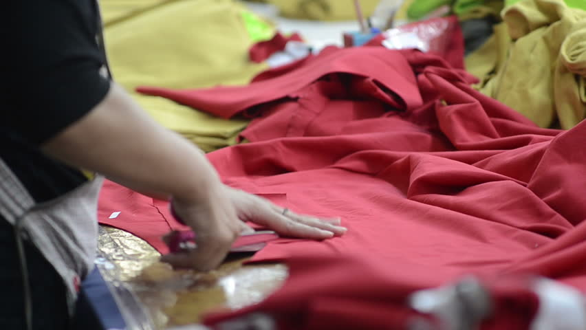 Close up shot of a woman cutting red fabric #1173598