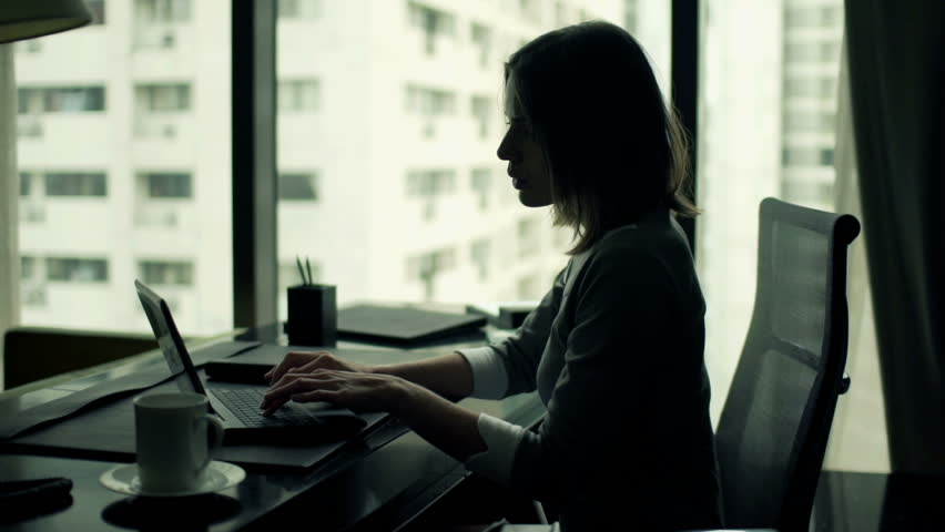 Young businesswoman using modern laptop sitting by desk office
