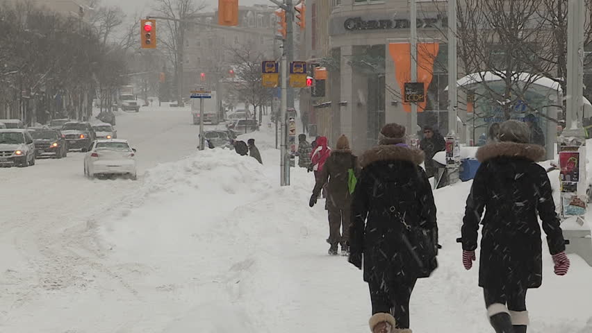 Waterloo, Ontario, Canada January 2014 Diverse people walking in blizzard snow wind  cold weather in major winter storm
