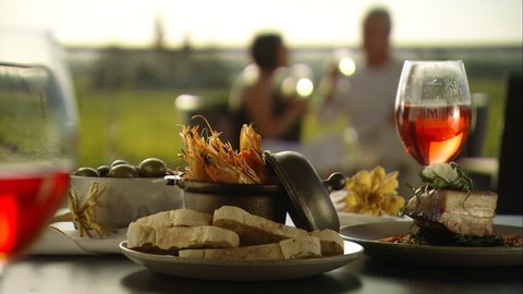 Footage of romantic couple alfresco fine dining meal outdoors amongst vineyards in winery with wine on table, seafood menu with vine views. Australian tourism in Barossa, Clare, Hunter, Yarra, Valley