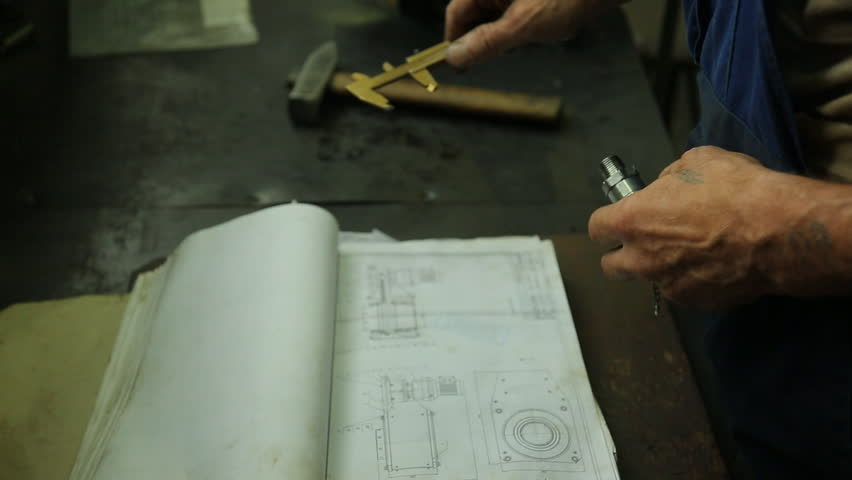 close up of a man checking the accuracy of the technique of manufacture of the product, which is at his workplace, he discovered records of the details in the hands of a tool to measure the exact size