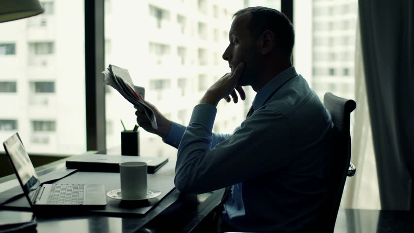Young businessman reading newspaper and drinking coffee sitting by desk in office  | Shutterstock HD Video #11827208