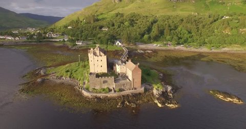 Stunning aerial shot of Eilean Donan castle in the Scottish highlands during good light with reflections of the castle in the water
