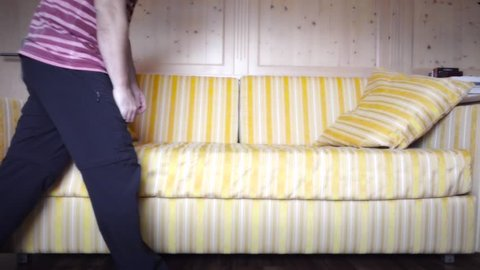 Caucasian man crashing down on couch to sleep in super slow motion