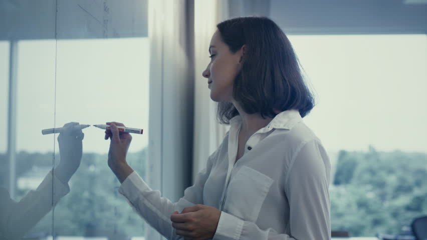 Young Female Office Worker in White Shirt is Writing on Glass Whiteboard. Shot on RED Cinema Camera in 4K (UHD).