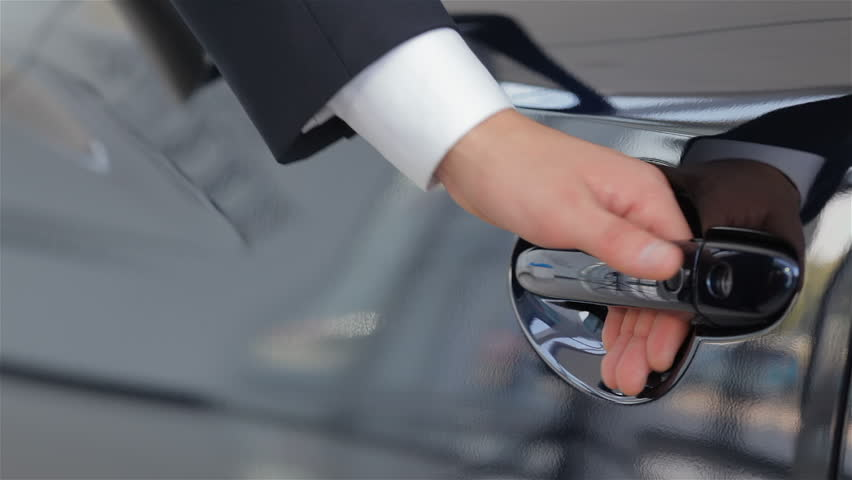Close up human hand opening car door. Auto business, car sale, technology and people concept - happy male with car dealer in auto show or salon. Young man with a salesman in a motor show. | Shutterstock HD Video #11918828