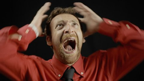 A man showing a screaming expression. Medium close-up shot of the face on black background. Part of a series of depictions of feelings and emotions with professional actors.