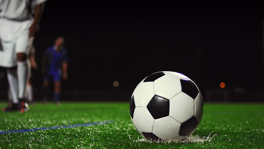 Close up of a soccer ball being kicked in slow motion at night #11951138