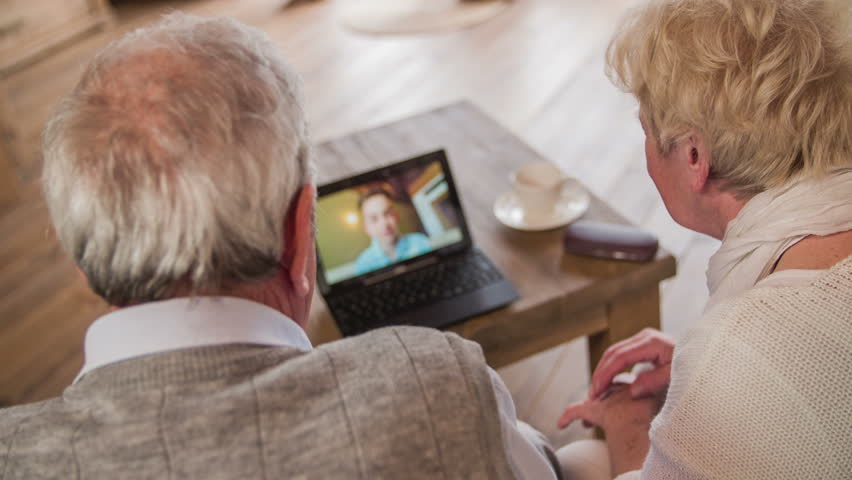 Grandparents talk to grandson over laptop video call 4K. Jib shot behind elderly couple sit on sofa with laptop computer on table and having a conversation with boy on screen. Live view skype chat.
