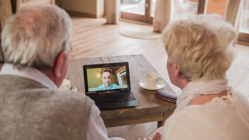 Boy waving over video call with grandparents 4K. Over shoulder view of elderly couple calling grandson with video call on laptop computer. Laptop on wooden desk. Two person sit on sofa.