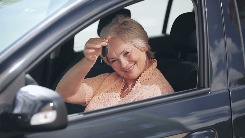 New Car: Senior attractive woman win or buy a new modern car and joy