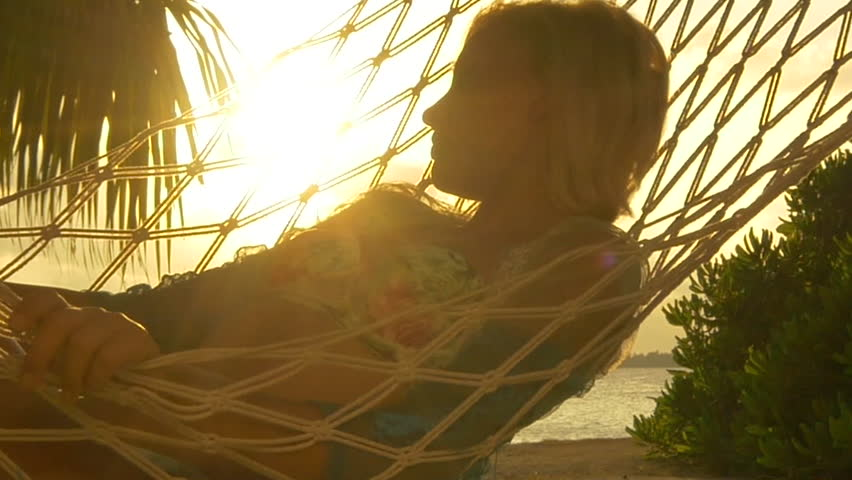 SLOW MOTION: Woman lying in hammock on beautiful exotic beach at golden sunset in paradise Maldives island