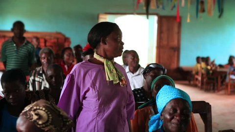 Kenya, Africa - April, 2013: A woman standing in the middle of a church congregation speaks while those around her listen. Filmed in Kenya, Africa.