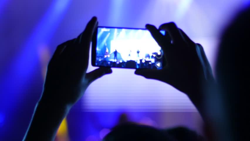 BLAGOEVGRAD, BULGARIA - SEP 26, 2015 - Free public music concert - Spectator shooting video via cell phone camera of a concert performance