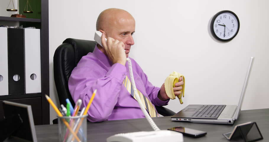Serious Businessman In Office Room Working Laptop And Eating A Sweet ...