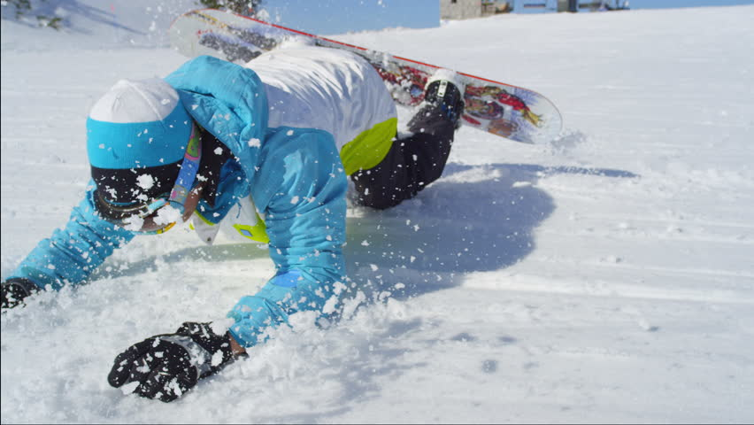 SLOW MOTION CLOSE UP: Snowboarder riding and falling on ski slope in sunny ski resort