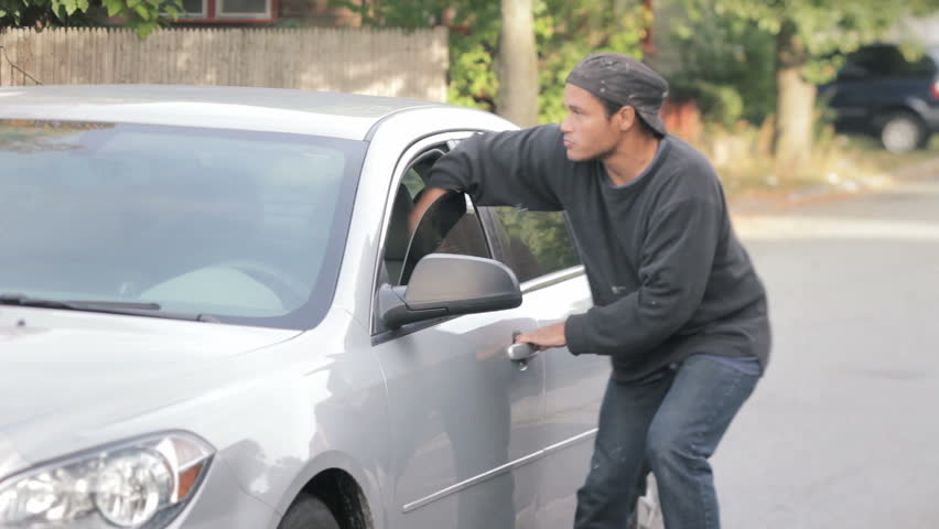 Crime concept, criminal thief stealing bag from parked car