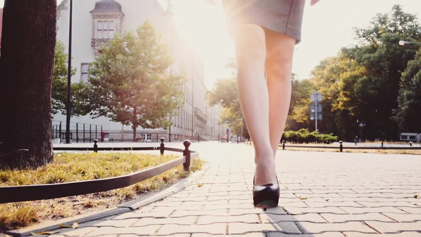 Sexy woman legs in black high-heeled shoes. Steadicam stabilized shot, Slow motion. Lens flare. Attractive businesswoman walking in the city in the morning. #12038468