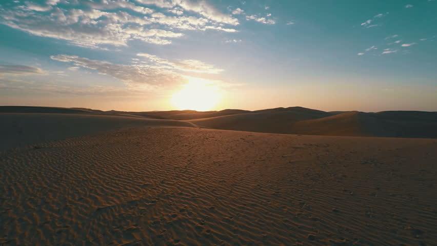 Flying low over the desert towards the sun