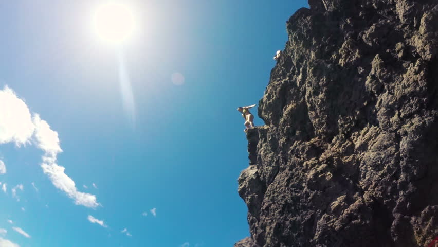 Group of friends jumping from cliff into the ocean in Hawaii. Water Shot Underwater Angle POV. Two Girls Jump Off Cliff into Ocean in Bikinis. Summer fun lifestyle.
