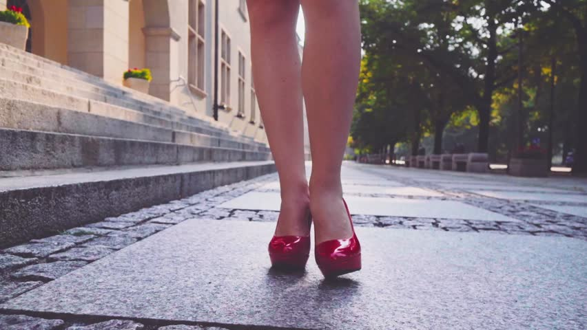 Attractive business woman with digital tablet walking in the city and drinking coffee in the morning. Steadicam stabilized shot in Slow motion. Lens flare. Confident woman in red high-heel shoes. #12063518