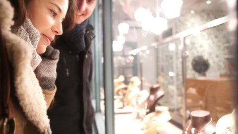 Attractive romantic couple shopping in the city at Christmas time. Shot on RED Epic.