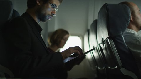 Young man is using a tablet on an airplane and a woman is reading in the background next to a window. Shot on RED Cinema Camera in 4K (UHD).