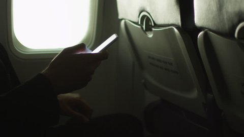 Young man in close-up is using a smartphone inside an airplane next to a window. Shot on RED Cinema Camera in 4K (UHD).