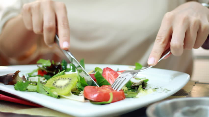 Woman eating salad, close up