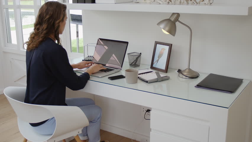 home office technology. successful woman working in modern home office with laptop computer and mobile phone technology emails connectivity for entrepreneur business stock