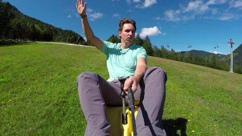 Happy young man enjoying summer sledge rollercoaster in nature