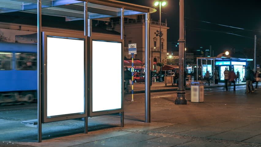 Ad space at the tram station at night. People pass by and watch. It is easily applied poster on a blank white background. Zagreb, Croatia - The main railway station | Shutterstock HD Video #12155378