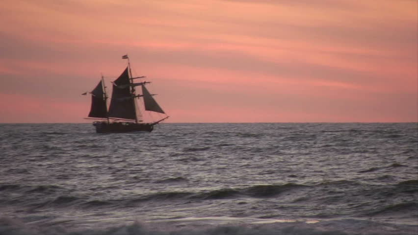 A tall ship sailing across the sea at sunset.