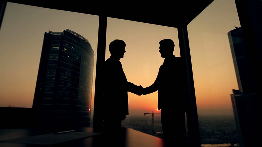 Silhouette of two businessmen talking and shaking hands standing by the window at sunset, the construction of a skyscraper and crane in the background | Shutterstock HD Video #12178604
