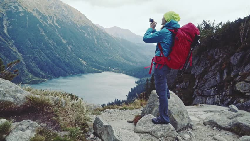Hiker woman taking picture with smart phone from mountain peak with lake view. Tourist using photo app, touching screen. Stabilized Slow Motion 120 fps. Epic Steadicam shot. Misty Mountains Series.  | Shutterstock HD Video #12185996