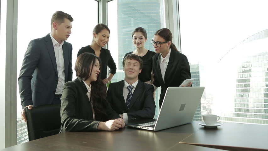 The office staff during working hours discussing the news on social networks using laptop | Shutterstock HD Video #12187217