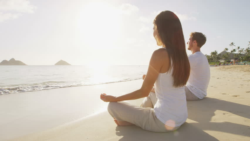 Meditation. Yoga people by the sea relaxing in serene zen lotus yoga pose on a beach at sunrise. Woman and man meditating together. | Shutterstock HD Video #12193784