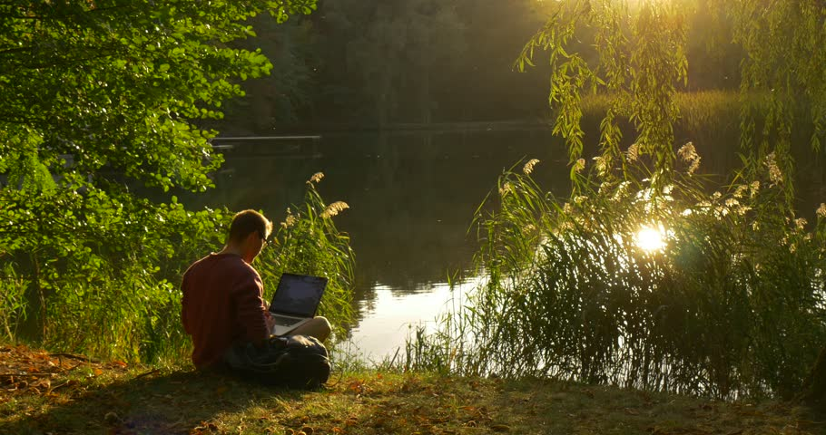 Man in Glasses is Working with Laptop, Sitting at The Lake With His Face to the Sun, Freelancer Programmer Copywriter Designer Accountant, Put the Laptop Away, looking at the water, Forest Lake,