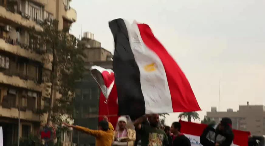 CAIRO - CIRCA JAN 2011: Man waves Egyptian flag, Tahrir Square, circa January 2011, Cairo, Egypt. Tahrir Square was the focal point of the 2011 Egyptian Revolution where demonstrations grew to 250,000 plus people by day 6, January 31, 2011.