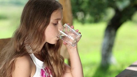 Beautiful girl drinks pure water from a glass