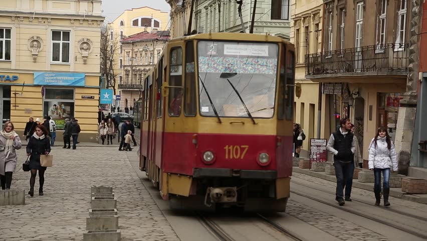 UKRAINE, LVIV, APRIL 5, 2015: Red tram and people near the Market Square - is a central square of the city of Lviv in Western Ukraine