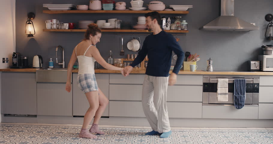Morning at home happy young couple newly wed dancing listening to music in kitchen wearing pajamas in love having fun | Shutterstock Video #12270179