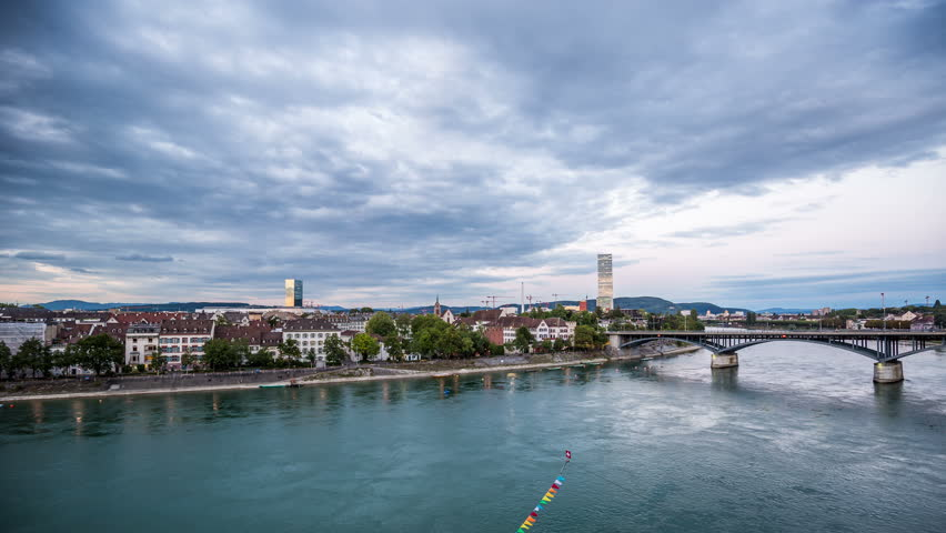 BASEL, SWITZERLAND – August 20, 2015: Basel skyline with, river, waterfront, sky with clouds in the evening timelapse, pan shot City skyline in the evening, day to night timelapse | Shutterstock HD Video #12274139