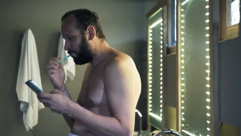 Young man in towel brushing teeth and texting on smartphone in bathroom