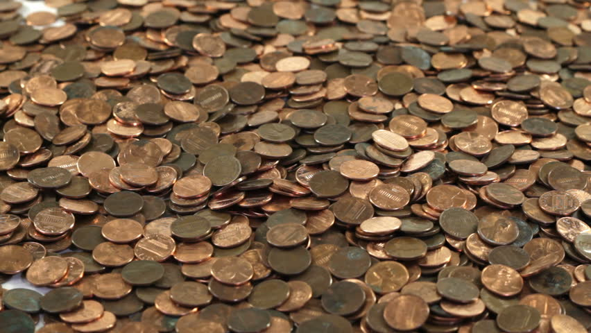 Thousands of pennies poured onto a table all at once.