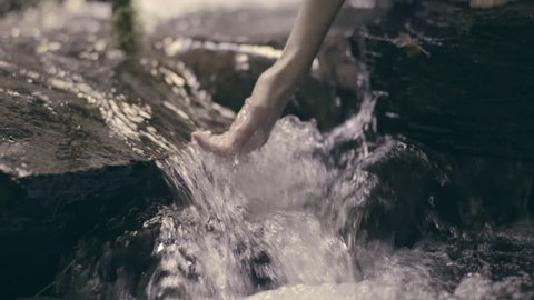 Young Woman Kneels Down In Stream, Scoops Up Water With Her Hand (Slow Motion)
