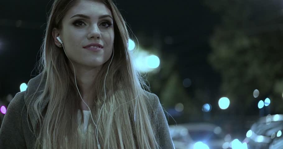 Woman listening music on cellphone walking evening time  | Shutterstock HD Video #12322118