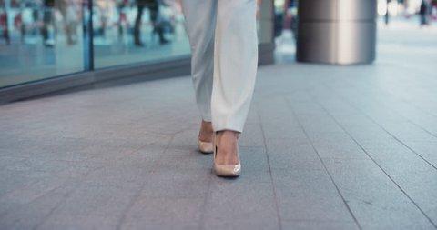 Smart business woman feet close crop walking to work entering glass corporate building wearing high heels urban city commuter concept