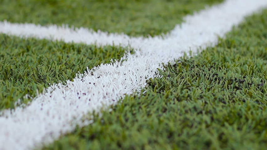 Close-up  of white markings on the green football ground in movement outdoors
